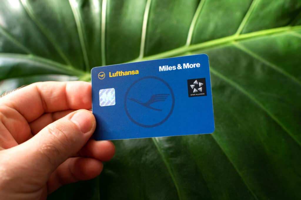Male hand holding Miles and More membership Lufthansa card